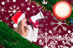 Composite image of festive blonde shouting through megaphone Royalty Free Stock Photography