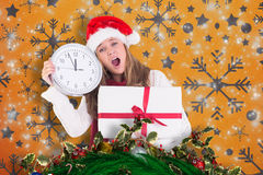 Composite image of festive blonde showing a clock and gift Royalty Free Stock Photography