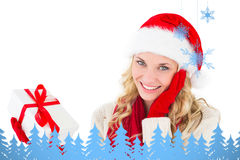 Composite image of festive blonde smiling at camera holding present Stock Images