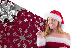 Composite image of festive blonde smiling and pointing Stock Image