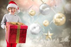 Composite image of festive boy holding gift Royalty Free Stock Photos