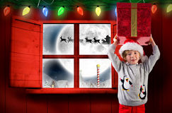Composite image of festive boy holding a gift Royalty Free Stock Photo