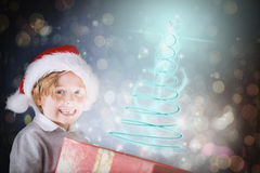 Composite image of festive boy opening gift Royalty Free Stock Photos