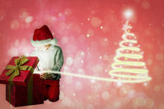 Composite image of festive boy opening gift Stock Photos