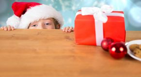 Composite image of festive boy peeking over table Royalty Free Stock Images
