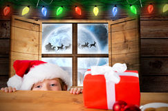 Composite image of festive boy peeking over table Royalty Free Stock Photo