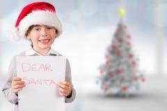 Composite image of festive boy showing letter Stock Image