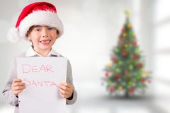 Composite image of festive boy showing letter Stock Photo