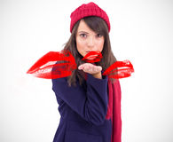 Composite image of festive brunette blowing a kiss Stock Image