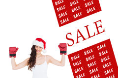 Composite image of festive brunette in boxing gloves with arms raised Royalty Free Stock Photography