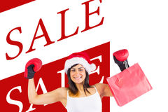 Composite image of festive brunette in boxing gloves holding shopping bags Stock Photography