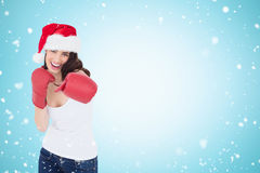 Composite image of festive brunette in boxing gloves punching Royalty Free Stock Image