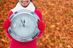 Composite image of festive brunette holding clock Royalty Free Stock Photos