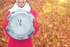 Composite image of festive brunette holding clock Stock Photos