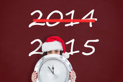 Composite image of festive brunette holding a clock Royalty Free Stock Images