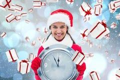 Composite image of festive brunette holding clock Royalty Free Stock Images