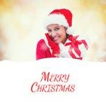 Composite image of festive brunette holding gift Stock Photos