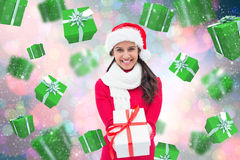 Composite image of festive brunette holding gift Stock Photo