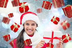 Composite image of festive brunette holding gift Royalty Free Stock Images