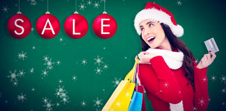 Composite image of festive brunette holding shopping bags and credit card Royalty Free Stock Photos