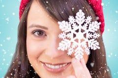 Composite image of festive brunette holding snowflake decoration Stock Image