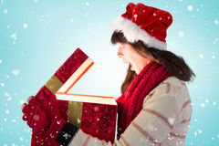 Composite image of festive brunette opening a glowing christmas gift Stock Photos