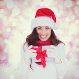 Composite image of festive brunette in santa hat holding gift Stock Photography