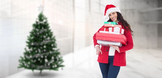 Composite image of festive brunette in santa hat and red coat holding pile of gifts Royalty Free Stock Image