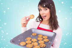 Composite image of festive brunette showing hot cookies Royalty Free Stock Photo