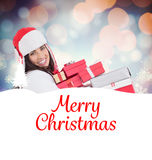 Composite image of festive brunette in winter clothes holding many gifts. Festive brunette in winter clothes holding many gifts against glowing christmas Stock Photo