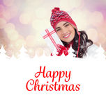 Composite image of festive brunette in winter clothes pointing gift. Festive brunette in winter clothes pointing gift against glowing christmas background Stock Image