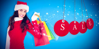 Composite image of festive brunette in winter wear holding shopping bags Royalty Free Stock Images