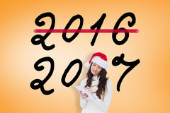 Composite image of festive brunette writing her christmas list Stock Photo