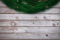 Composite image of festive christmas wreath. Festive christmas wreath against digitally generated grey wooden planks Stock Image