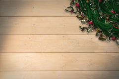Composite image of festive christmas wreath with decorations. Festive christmas wreath with decorations against bleached wooden planks background Stock Photography
