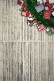 Composite image of festive christmas wreath with decorations. Festive christmas wreath with decorations against digitally generated grey wooden planks Stock Images