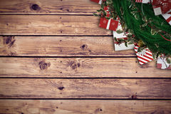 Composite image of festive christmas wreath with decorations. Festive christmas wreath with decorations against wooden planks background Stock Images