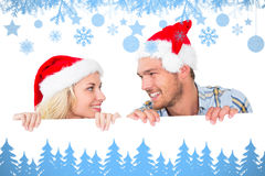 Composite image of festive couple smiling from behind poster. Festive couple smiling from behind poster against snow flake frame in blue Stock Images