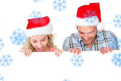 Composite image of festive couple smiling from behind poster. Festive couple smiling from behind poster against snowflakes Royalty Free Stock Photo