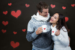 Composite image of festive couple smiling and holding mugs Royalty Free Stock Photos