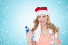 Composite image of festive fit blonde holding bottle of water. Festive fit blonde holding bottle of water against christmas snow falling Stock Images