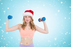 Composite image of festive fit blonde holding dumbbells. Festive fit blonde holding dumbbells against christmas snow falling Stock Photos
