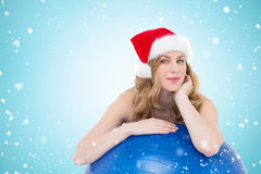 Composite image of festive fit blonde leaning on exercise ball. Festive fit blonde leaning on exercise ball against christmas snow falling Stock Photography