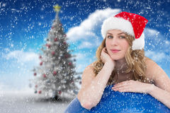 Composite image of festive fit blonde leaning on exercise ball. Festive fit blonde leaning on exercise ball against christmas tree in snowy landscape Royalty Free Stock Image