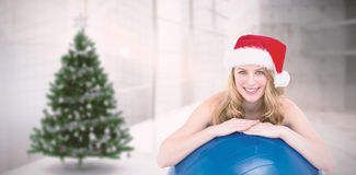 Composite image of festive fit blonde leaning on exercise ball. Festive fit blonde leaning on exercise ball against home with christmas tree Royalty Free Stock Images