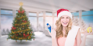 Composite image of festive fit blonde smiling at camera. Festive fit blonde smiling at camera against home with christmas tree Royalty Free Stock Photography