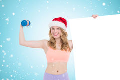 Composite image of festive fit blonde smiling at camera holding poster. Festive fit blonde smiling at camera holding poster against christmas snow falling Stock Photos
