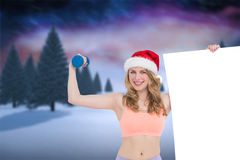 Composite image of festive fit blonde smiling at camera holding poster Stock Photos