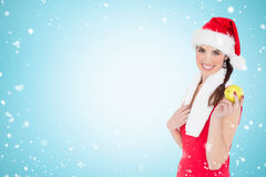 Composite image of festive fit brunette holding apple. Festive fit brunette holding apple against christmas snow falling Royalty Free Stock Photography