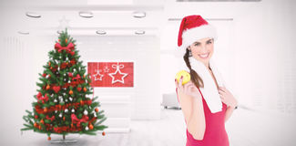 Composite image of festive fit brunette holding apple. Festive fit brunette holding apple against home with christmas tree Stock Photos